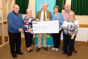 Sean and Rosemary present charity cheques in Dunloy Parish Hall